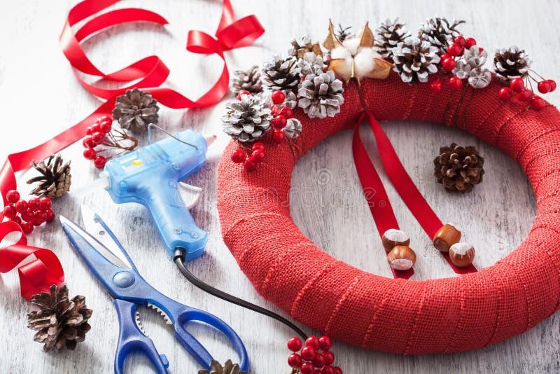 Καθιστώντας την κόκκινη διακόσμηση στεφανιών Χριστουγέννων diy χειροποίητο στοκ εικόνα με δικαίωμα ελεύθερης χρήσης