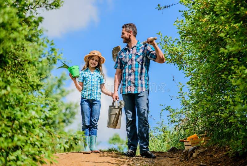 Καθιστώντας τον κόσμο πράσινο το φτυάρι και το πότισμα μπορούν εργαζόμενος παιδιών με το κιβώτιο λαβής μπαμπάδων οικογενειακή σύν στοκ φωτογραφία