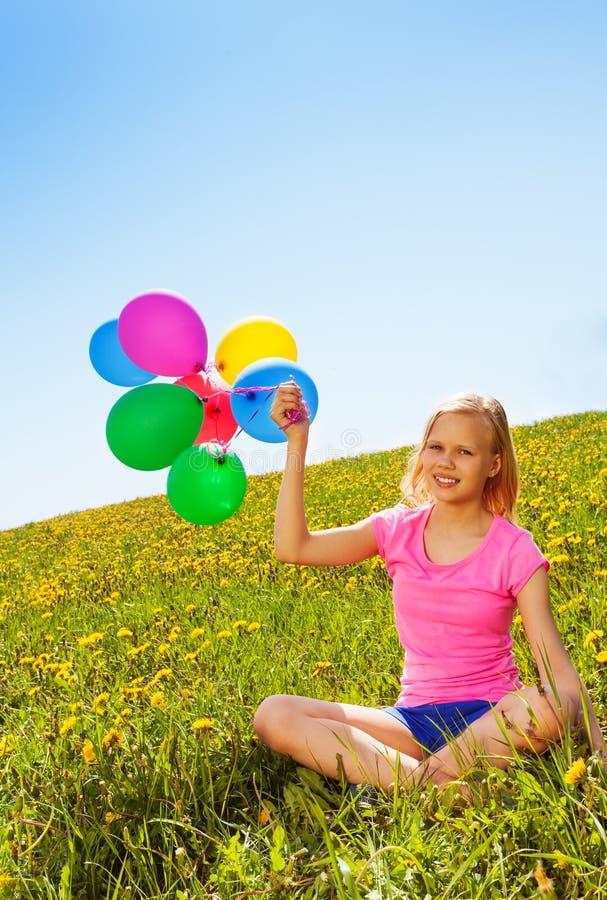 Καθμένος θετικό κορίτσι με τα μπαλόνια το καλοκαίρι στοκ εικόνα