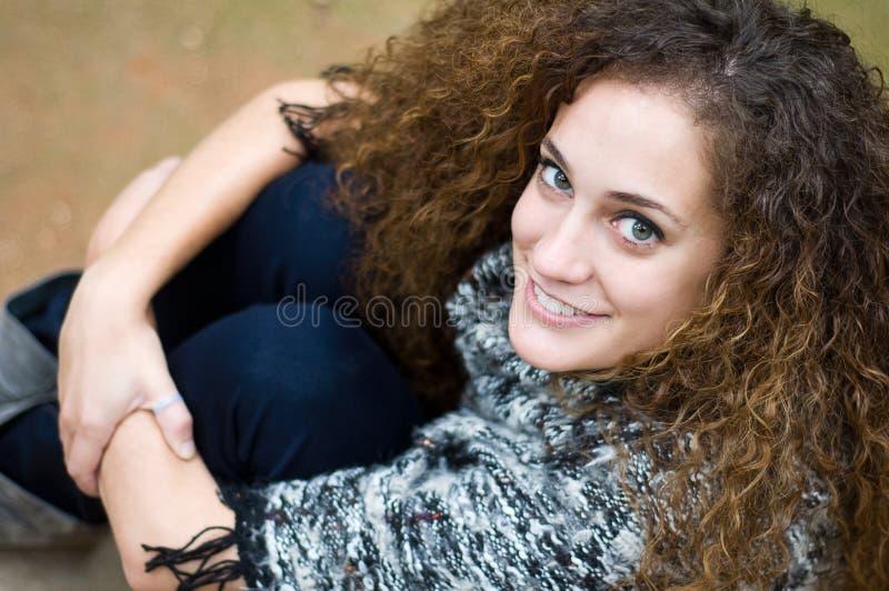 Καθμένος χαμογελώντας νέα γυναίκα στοκ εικόνα με δικαίωμα ελεύθερης χρήσης
