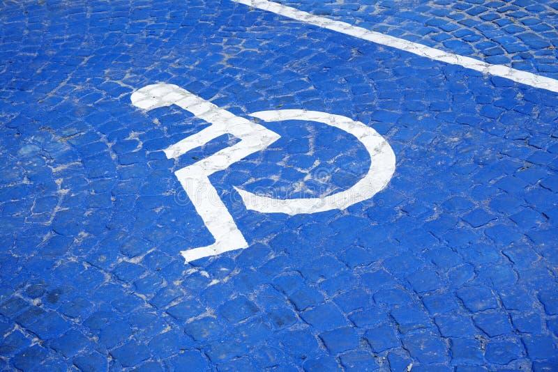 Καθολικό σημάδι για το σημείο χώρων στάθμευσης αναπηρίας η αναπηρική καρέκλα με το σημάδι πληροφοριών στο υπόβαθρο πατωμάτων για  στοκ φωτογραφία