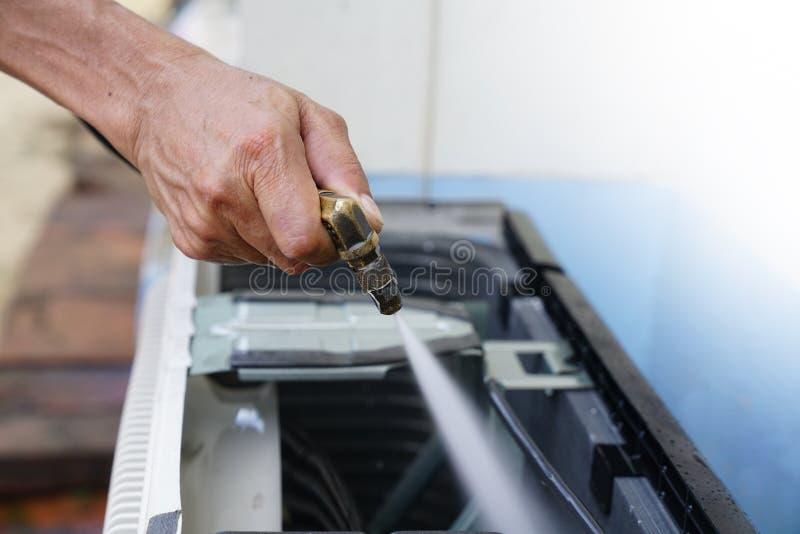 Καθορίζοντας και καθαρίζοντας κλιματιστικών μηχανημάτων μονάδα μηχανικών ή επισκευαστών στοκ εικόνα