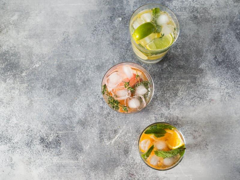 Καθορισμένα θερινά κρύα ποτά με τα διαφορετικά εσπεριδοειδή στα γυαλιά σε ένα γκρίζο υπόβαθρο Κοκτέιλ με το γκρέιπφρουτ, το πορτο στοκ φωτογραφίες