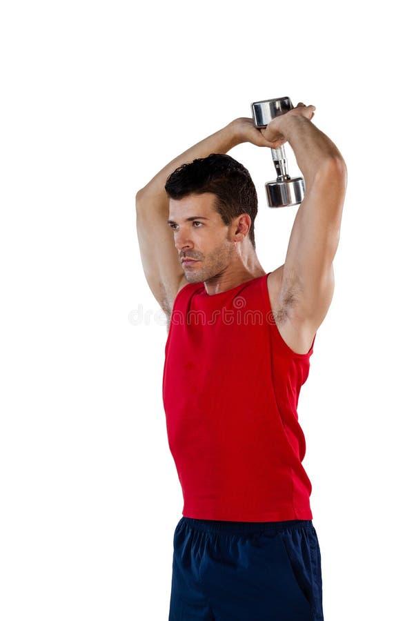 Καθορισμένος αθλητικός φορέας που ασκεί με τα dumbells στοκ φωτογραφία