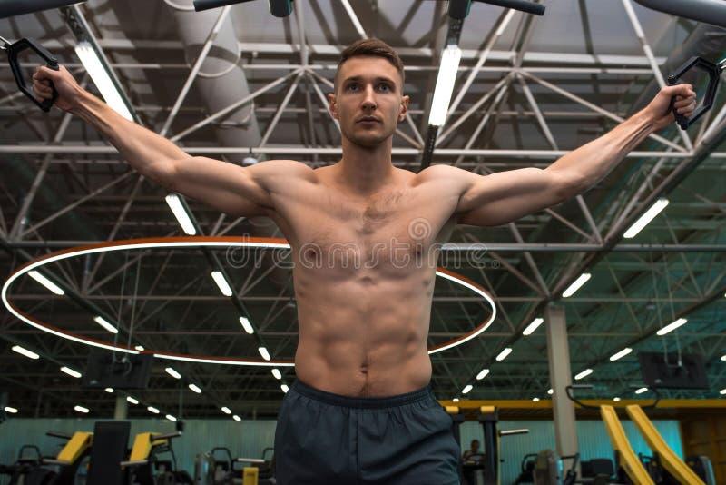 Καθορισμένος νεαρός άνδρας που επιλύει στη γυμναστική στοκ εικόνα