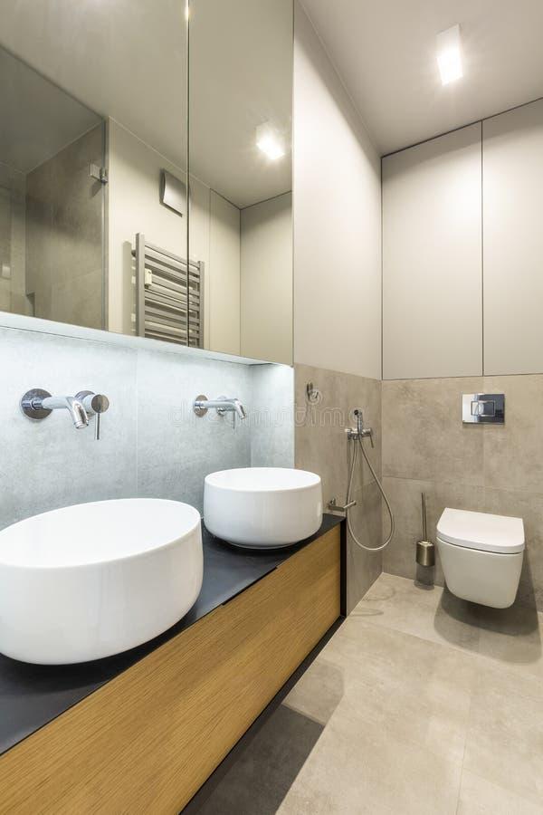 Καθρέφτης επάνω από washbasin στο μπεζ κομψό εσωτερικό λουτρών με το λ στοκ φωτογραφία με δικαίωμα ελεύθερης χρήσης