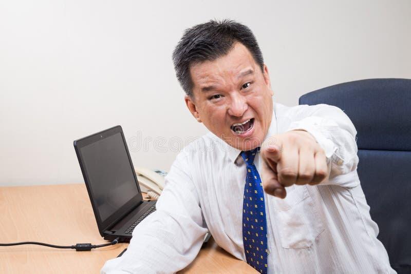 0 και αγχωτικός ασιατικός διευθυντής που φωνάζει και που δείχνει σε offic στοκ εικόνες