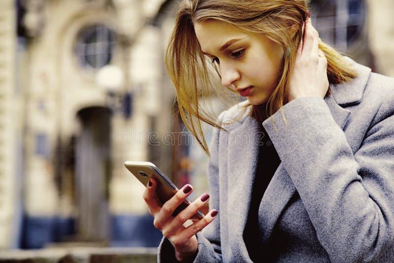 και λυπημένη νέα γυναίκα που εξετάζει το τηλέφωνο κυττάρων που βλέπει το κακό κείμενοη στοκ φωτογραφίες