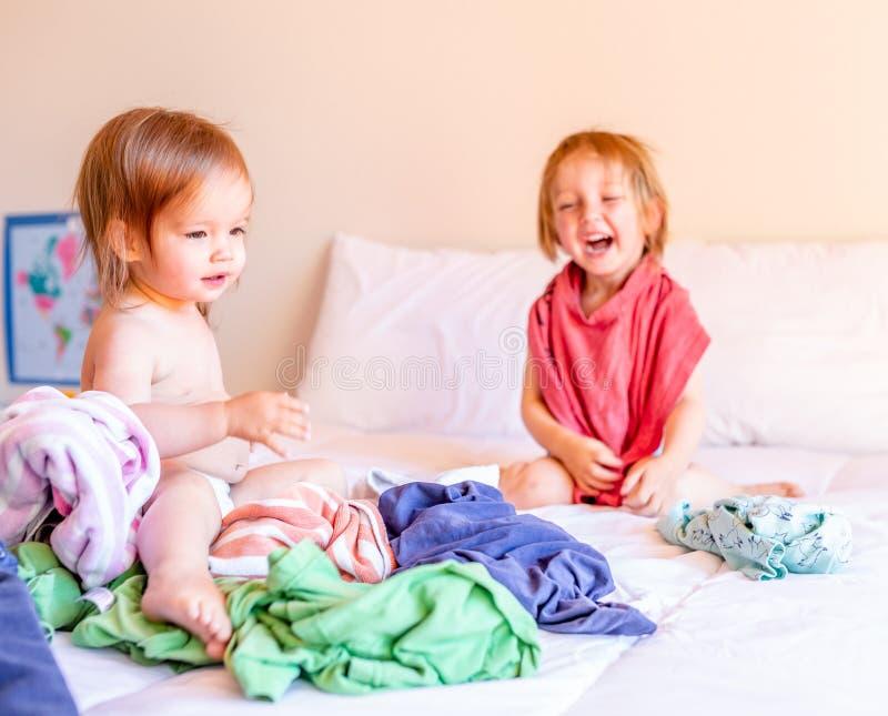 Κακό παιχνίδι αδελφών και αδελφών σε έναν σωρό του πλυντηρίου στο κρεβάτι Οικογενειακή έννοια στοκ εικόνα με δικαίωμα ελεύθερης χρήσης