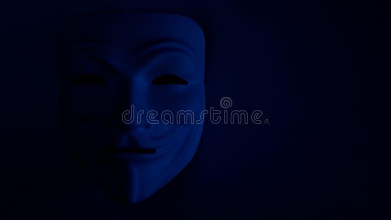 Κακώς ορατή μάσκα σε ένα σκοτεινό υπόβαθρο στο μπλε Ένα ανώνυμο σύμβολο χάκερ ή κομμάτων αποκριών r Πυροβολώντας ένα θέμα μέσα στοκ εικόνα