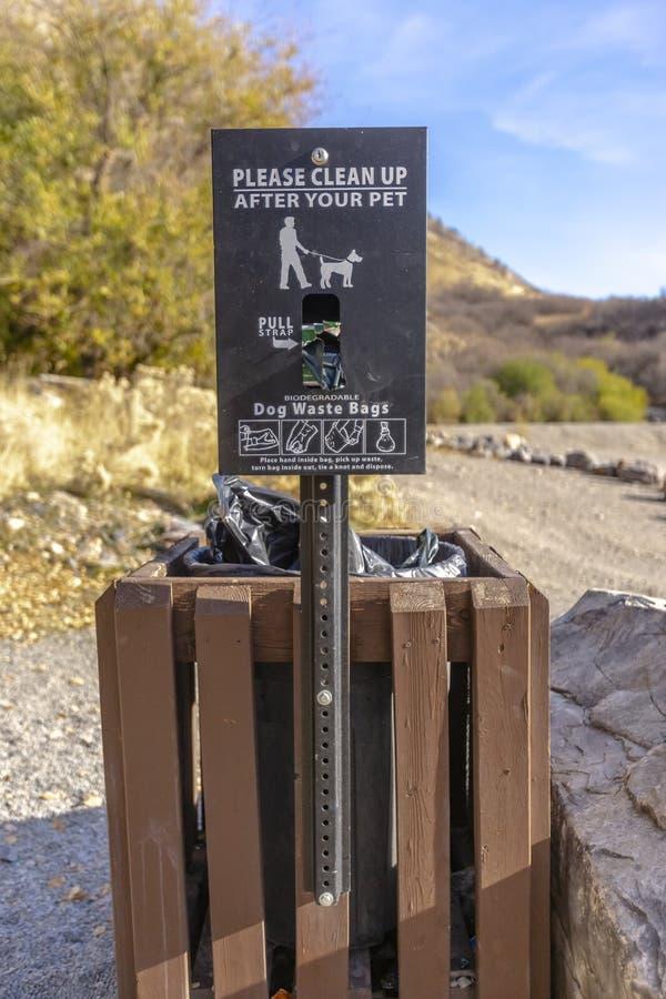 Καλάθι αποβλήτων σκυλιών με ένα σημάδι που διαβάζει παρακαλώ καθαρό επάνω μετά από τα κατοικίδια ζώα σας στοκ φωτογραφία