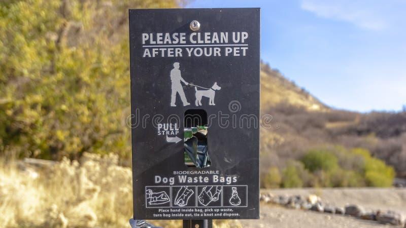 Καλάθι αποβλήτων σκυλιών πλαισίων πανοράματος με ένα σημάδι που διαβάζει παρακαλώ καθαρό επάνω μετά από τα κατοικίδια ζώα σας στοκ εικόνες με δικαίωμα ελεύθερης χρήσης