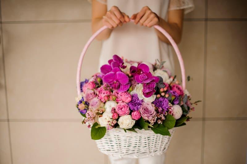 Καλάθι με τα διαφορετικά λουλούδια στα χέρια της γυναίκας στοκ εικόνες με δικαίωμα ελεύθερης χρήσης