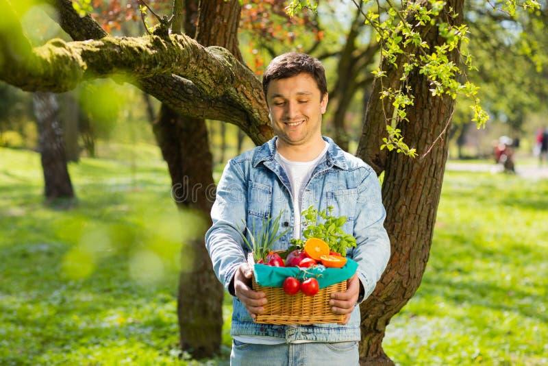 Καλάθι με τα λαχανικά και τα φρούτα στα χέρια ενός υποβάθρου αγροτών της φύσης concept healthy lifestyle στοκ φωτογραφία με δικαίωμα ελεύθερης χρήσης