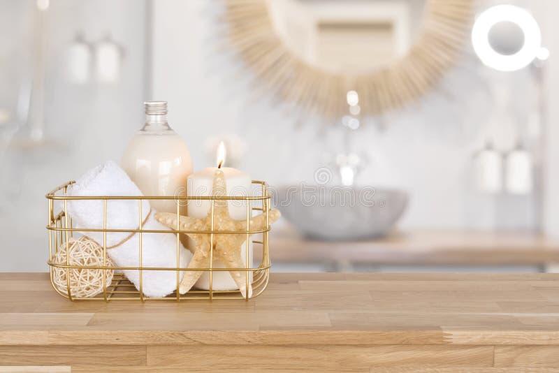 Καλάθι με τα προϊόντα SPA στο ξύλο πέρα από το θολωμένο εσωτερικό λουτρών στοκ εικόνα