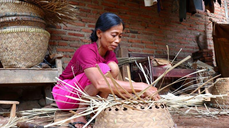 Καλάθι μπαμπού craftswoman κάνοντας την εργασία του στοκ φωτογραφίες