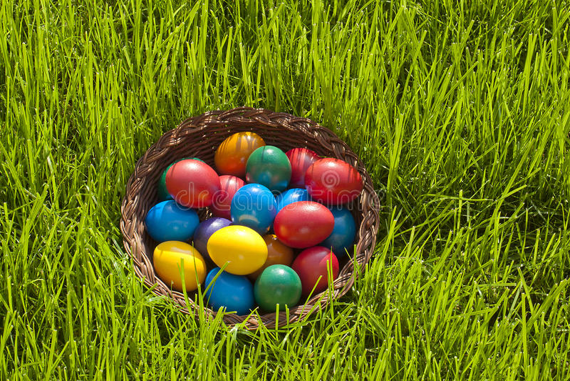Καλάθι των ζωηρόχρωμων αυγών Πάσχας στοκ εικόνες