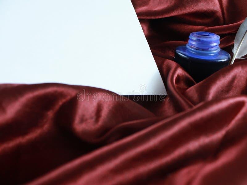 Καλάμι στο κόκκινο σατέν μεταξιού με το μελάνι και τη Λευκή Βίβλο στοκ φωτογραφία με δικαίωμα ελεύθερης χρήσης