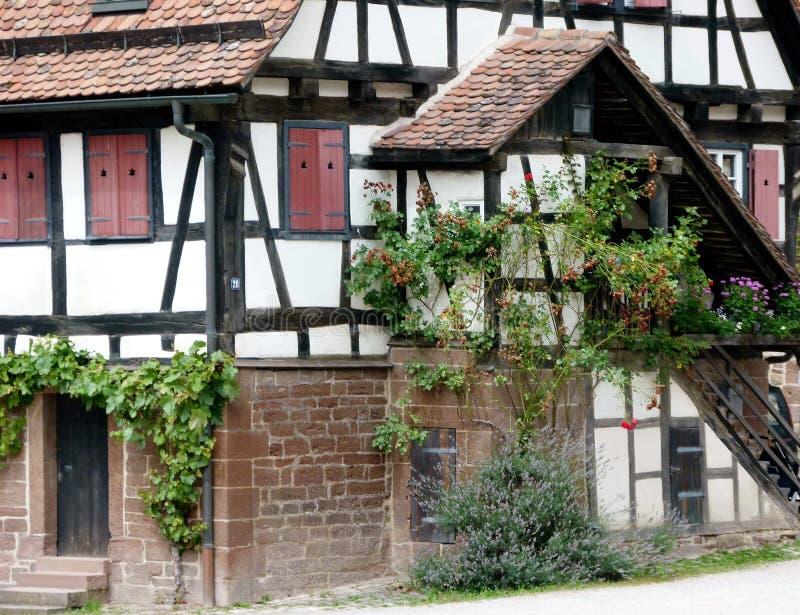 Καλά διατηρημένο μισό-εφοδιασμένο με ξύλα σπίτι με μια καλυμμένη σκάλα και κλειστά παραθυρόφυλλα στοκ εικόνα