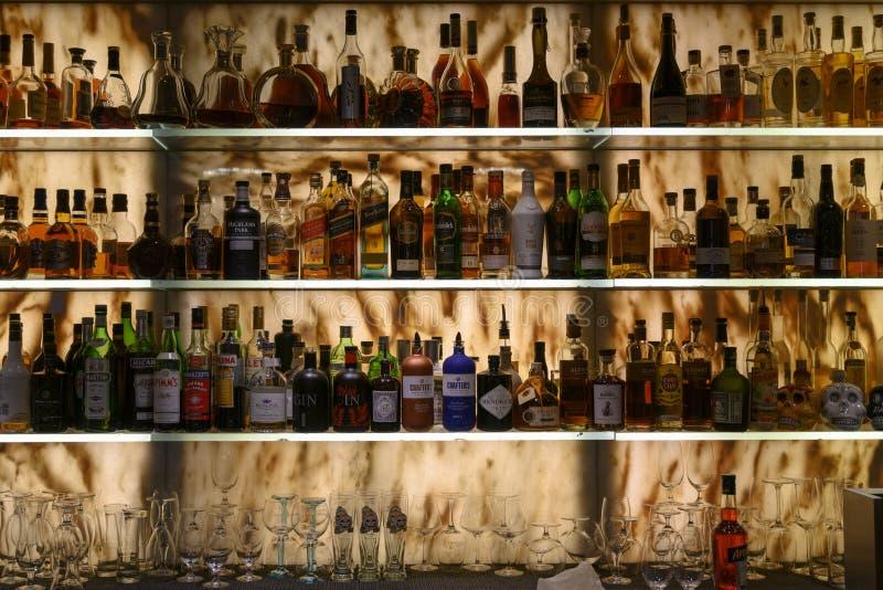 Καλά εφοδιασμένος φραγμός με τα διάφορα οινοπνευματώδη μπουκάλια και τα γυαλιά στοκ φωτογραφία