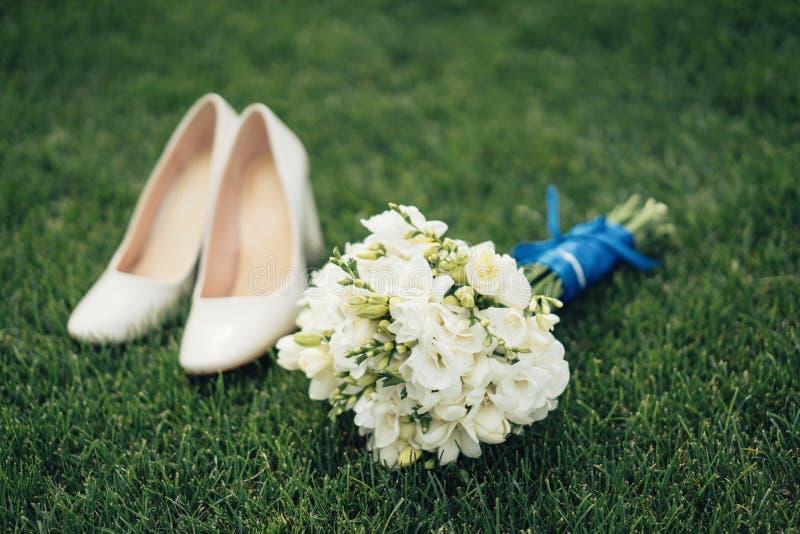 Καλά νυφικά παπούτσια ανθοδεσμών και νυφών σε μια πράσινη χλόη στοκ φωτογραφίες