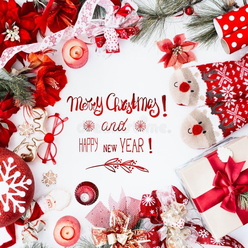 Καλά Χριστούγεννα και Ευτυχισμένος ο καινούργιος χρόνος με κόκκινα χριστουγεννιάτικα στολίδια, αστείες κάλτσες ελαφιού και κουτί  στοκ φωτογραφίες