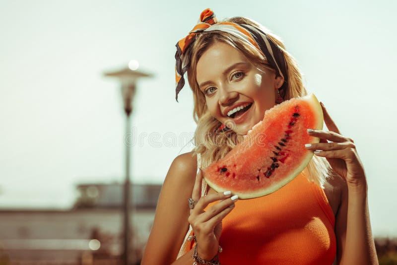 Καλή ακτινοβολώντας χαμογελώντας ακτινοβόλος ελκυστική κυρία που κρατά ένα κομμάτι καρπουζιών στοκ εικόνα