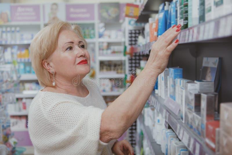 Καλή ανώτερη γυναίκα που ψωνίζει στο φαρμακείο στοκ φωτογραφία