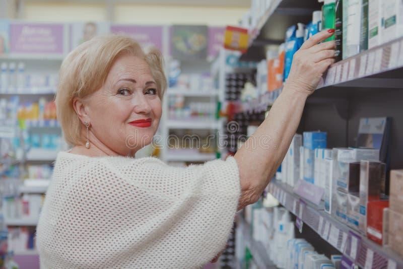 Καλή ανώτερη γυναίκα που ψωνίζει στο φαρμακείο στοκ εικόνες με δικαίωμα ελεύθερης χρήσης