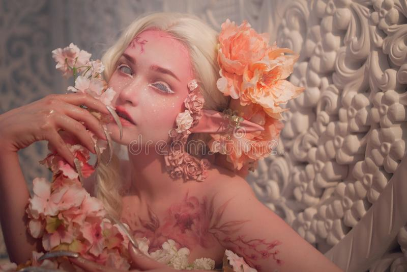 Καλή αυτή-νεράιδα μεταξύ των λουλουδιών Δημιουργική σύνθεση και bodyart στοκ φωτογραφία