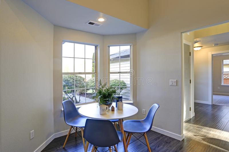 Καλή γωνία προγευμάτων με την άσπρη διάσκεψη στρογγυλής τραπέζης και τις μπλε καρέκλες στοκ εικόνες