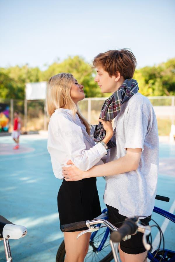 Καλή εξέταση αγοριών το όμορφο κορίτσι με τα ξανθά μαλλιά και αγκάλιασμα την στο πάρκο Νέο ζεύγος που στέκεται και χρόνος εξόδων στοκ εικόνες