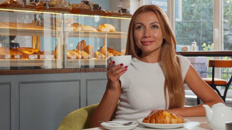 Καλή κοκκινομάλλης γυναίκα που απολαμβάνει τον καφέ και croissant το πρωί στοκ φωτογραφία με δικαίωμα ελεύθερης χρήσης