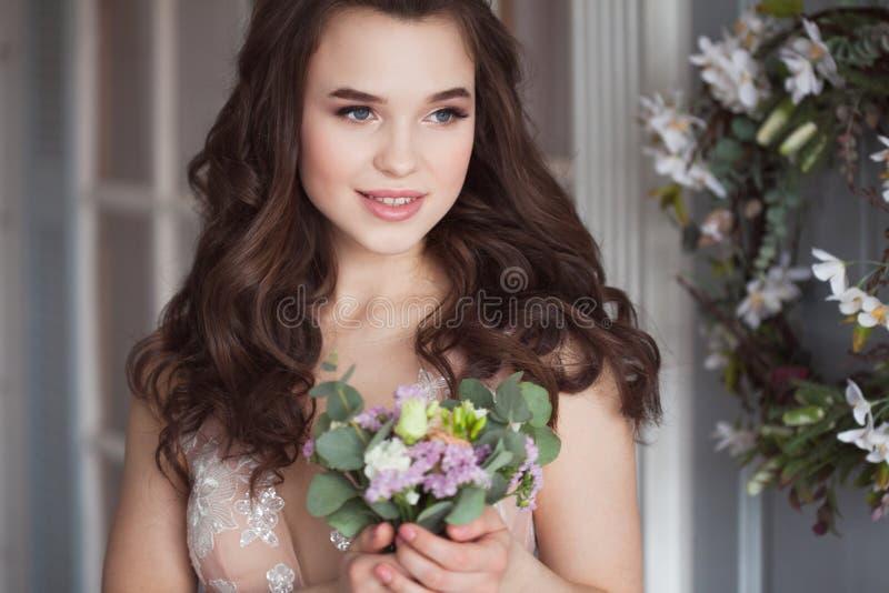 Καλή νέα γυναίκα σε ένα δαντελλωτός ρόδινο φόρεμα Ελκυστική νύφη με μια ανθοδέσμη των λουλουδιών στοκ φωτογραφία με δικαίωμα ελεύθερης χρήσης