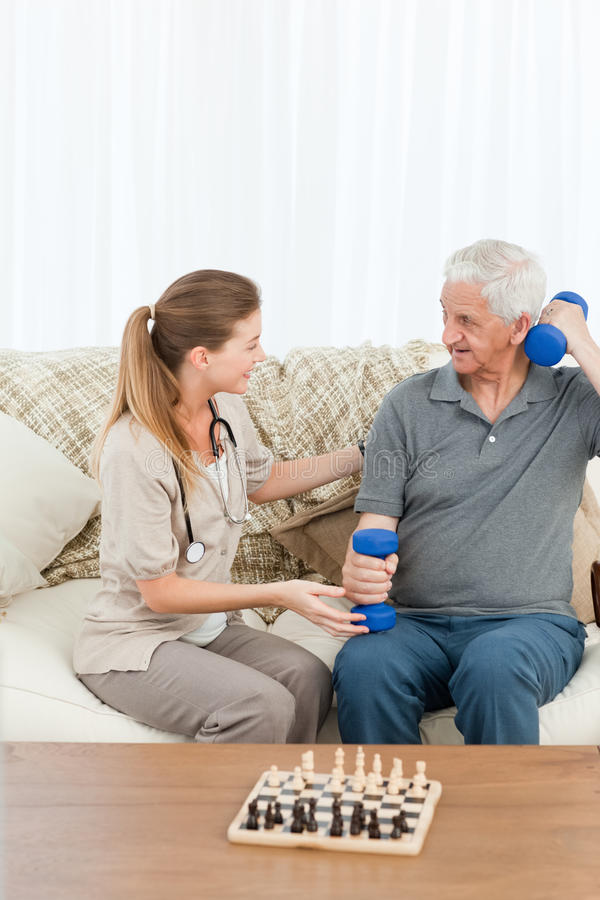 Καλή νοσοκόμα που βοηθά τον ασθενή της για να κάνει τις ασκήσεις στοκ φωτογραφία με δικαίωμα ελεύθερης χρήσης
