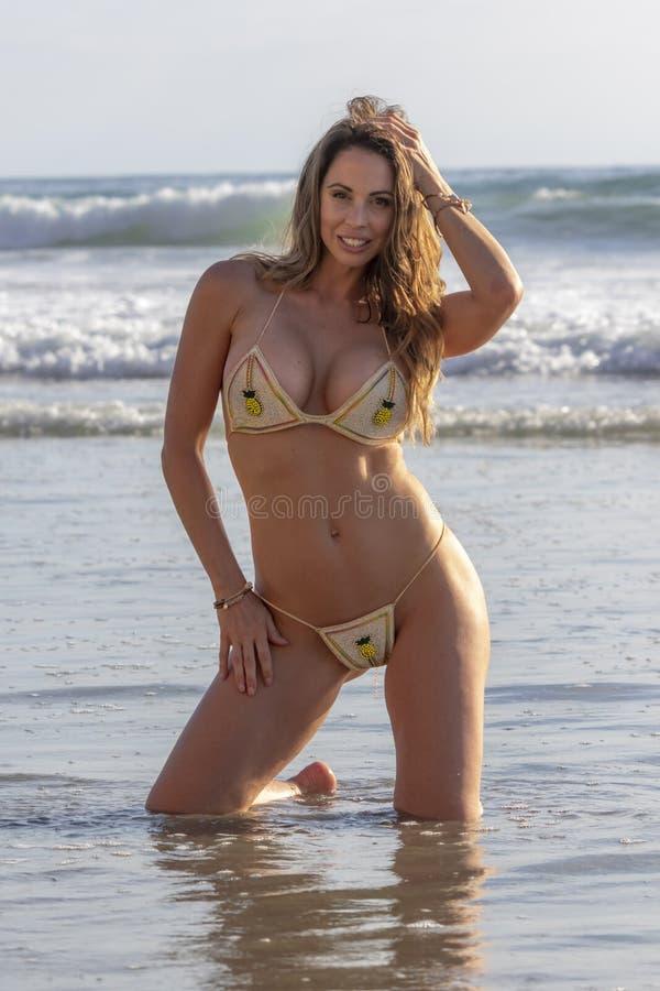 Καλή πρότυπη χαλάρωση μπικινιών Brunette στην παραλία στοκ φωτογραφία με δικαίωμα ελεύθερης χρήσης