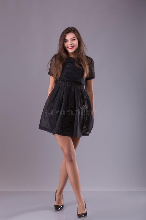 Καλή χαριτωμένη χαμογελώντας νέα γυναίκα στο μαύρο φόρεμα, τα κόκκινα χείλια και τα μακριά πόδια που στέκονται σε ένα γκρίζο υπόβ στοκ εικόνες