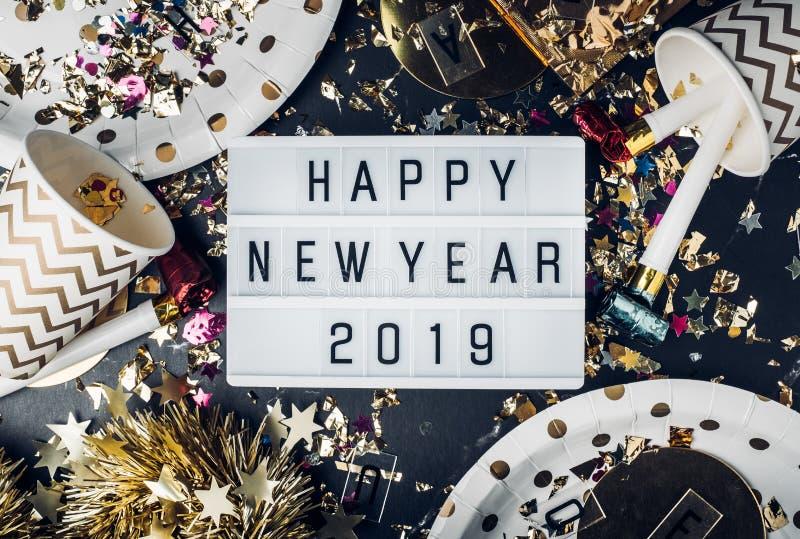 Καλή χρονιά 2019 στο ελαφρύ κιβώτιο με το φλυτζάνι κομμάτων, ανεμιστήρας κομμάτων, κασσίτερος στοκ εικόνα με δικαίωμα ελεύθερης χρήσης