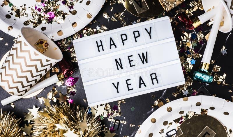 Καλή χρονιά στο ελαφρύ κιβώτιο με το φλυτζάνι κομμάτων, ανεμιστήρας κομμάτων, tinsel, κομφετί Η διασκέδαση γιορτάζει τη τοπ άποψη στοκ εικόνες με δικαίωμα ελεύθερης χρήσης