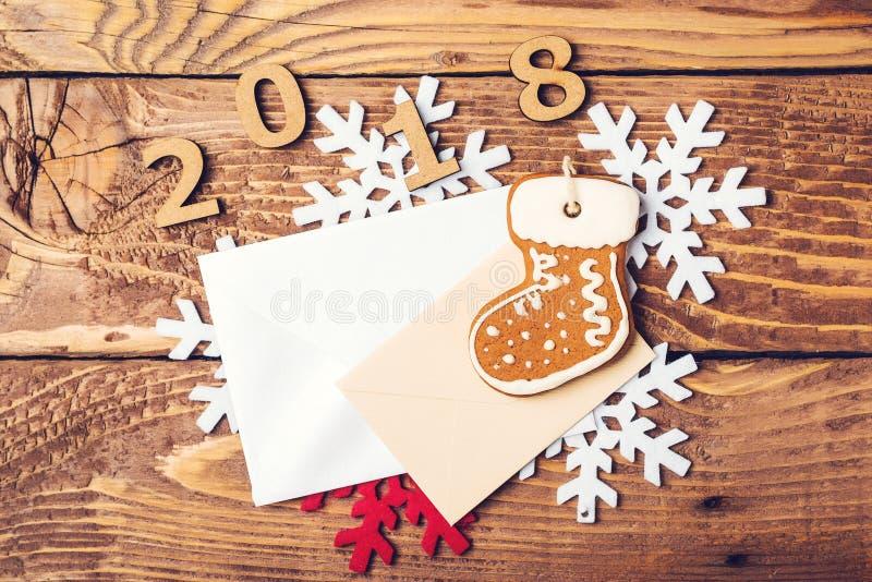 Καλή χρονιά 2018 Υπόβαθρο Χριστουγέννων με το φάκελο, μελόψωμο, snowflackes πέρα από τον ξύλινο πίνακα στοκ εικόνες