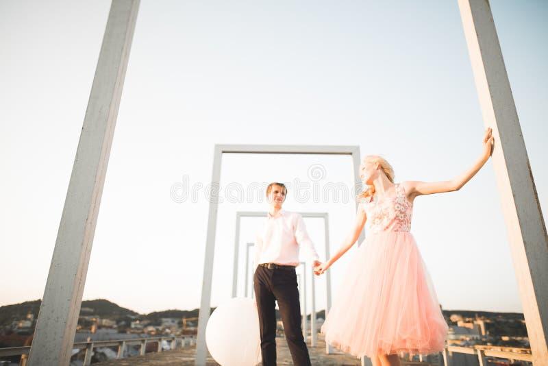 Καλή όμορφη τοποθέτηση ζευγών μόδας στη στέγη με το υπόβαθρο πόλεων Νεαρός άνδρας και αισθησιακός ξανθός υπαίθριος lifestyle στοκ φωτογραφίες με δικαίωμα ελεύθερης χρήσης