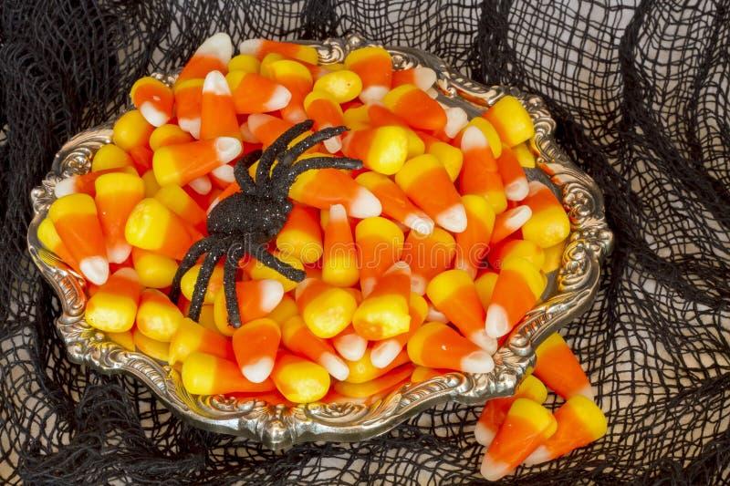 Καλαμπόκι και αράχνη καραμελών στο ασημένιο πιάτο στοκ εικόνα