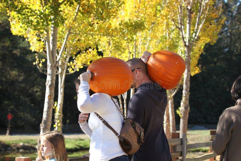 Καλιφόρνια ΗΠΑ Οκτωβρίου 2012 Μια νέα οικογένεια με τις κολοκύθες στους ώμους τους πηγαίνει να γιορτάσει αποκριές στοκ φωτογραφία με δικαίωμα ελεύθερης χρήσης