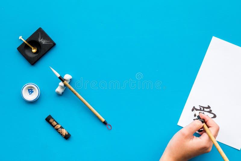 καλλιγραφία Το χέρι γράφει hieroglyph την αγάπη στη Λευκή Βίβλο για το μπλε διάστημα αντιγράφων άποψης υποβάθρου τοπ στοκ εικόνες με δικαίωμα ελεύθερης χρήσης