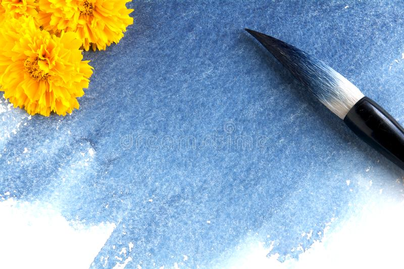 Καλλιγραφική βούρτσα που λεκιάζουν με το μπλε χρώμα σε ένα φύλλο του εγγράφου watercolor με το λεκέ λουλακιού στοκ φωτογραφίες