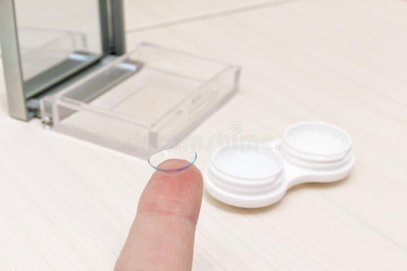 Καλλιεργημένα θηλυκά χέρια που παίρνουν τους φακούς επαφής από ένα εμπορευματοκιβώτιο στοκ φωτογραφίες