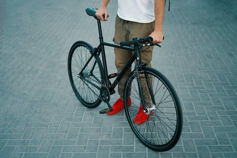 Καλλιεργημένα χέρια ατόμων εικόνας που κρατούν ένα ποδήλατο στεμένος κατά μέρος στοκ εικόνα