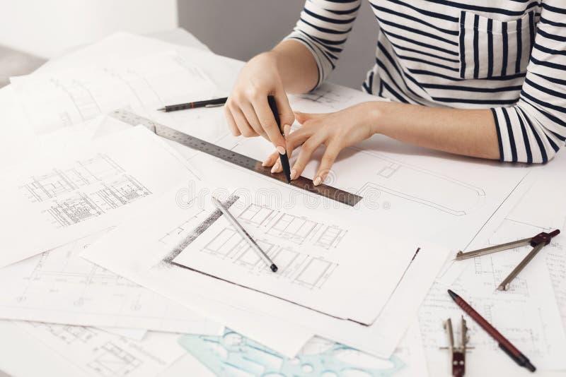 Καλλιεργημένη άποψη του νέου όμορφου θηλυκού σχεδιαστή που φορά την εξάρτηση λωρίδων, που κάθεται στη comfy ελαφριά θέση εργασίας στοκ εικόνα με δικαίωμα ελεύθερης χρήσης