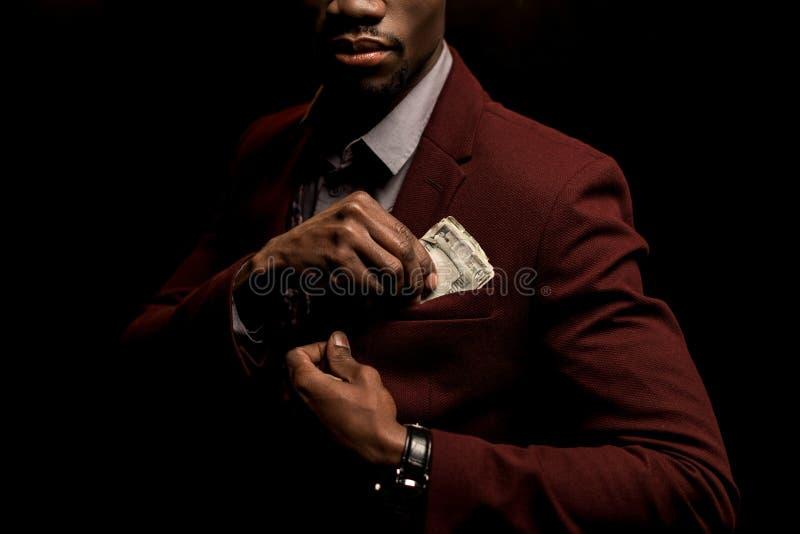 καλλιεργημένη άποψη του πλούσιου ατόμου αφροαμερικάνων που βάζει τα τραπεζογραμμάτια δολαρίων στην τσέπη στοκ φωτογραφία
