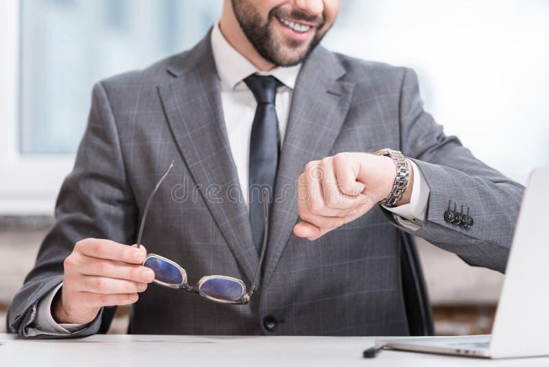καλλιεργημένη άποψη του χαμόγελου των γυαλιών εκμετάλλευσης επιχειρηματιών και του κοιτάγματος στοκ φωτογραφίες με δικαίωμα ελεύθερης χρήσης